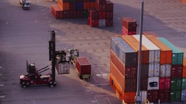 drohne schuss von top handler, die vermittlung von containern - entladen stock-videos und b-roll-filmmaterial