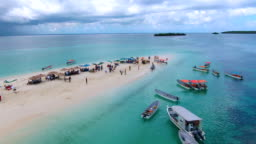 Drone shot of tropical sand island full of people and boats