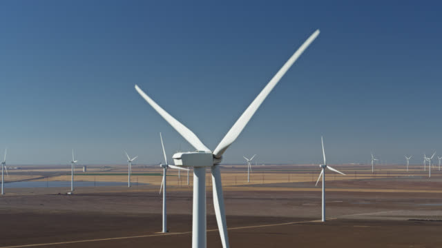 drone shot of turning blades on turbine at texas panhandle wind farm - propeller stock videos & royalty-free footage