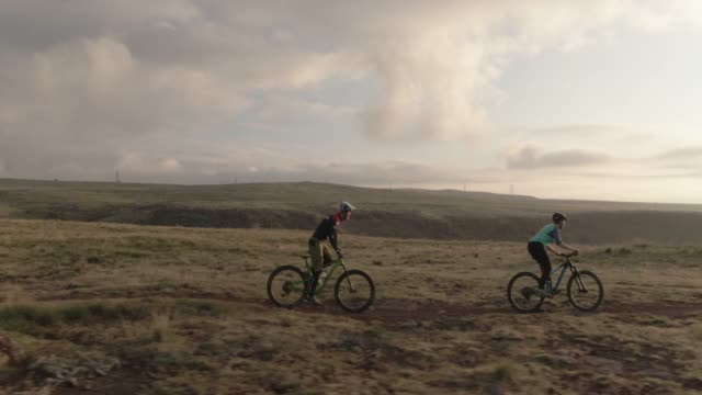 drone shot of two people (a female and a male )mountain biking on in the rocky mountains west of denver, colorado with the city below at sunrise - colorado stock videos & royalty-free footage