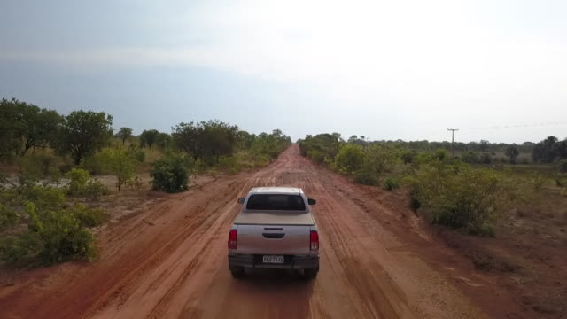drone shot of two pickup trucks driving along a wide track in the the cerrado savannah brazil - remote location stock videos & royalty-free footage
