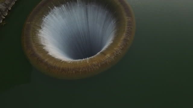 Drone shot of water flowing in bell mouth spillway at Lake Berryessa