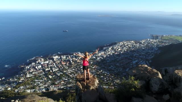 Drone shot of woman reaching mountain top