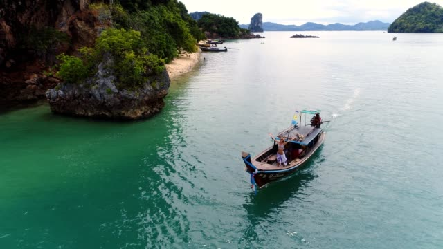 Drone shot of woman standing on a longtail boat in tropical settings