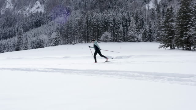 Drone shot of young woman cross country skiing in valley covered in snow surrounded with mountains