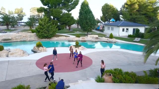 プールの前で太極拳クラスの若い女性のドローンショット - アニメーター点の映像素材/bロール