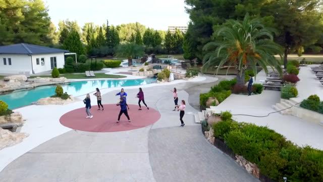 観光地の太極拳クラスの若い女性のドローンショット - アニメーター点の映像素材/bロール