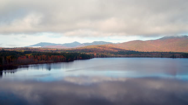 drone shot over a lake with reflections in fall - new hampshire stock videos & royalty-free footage