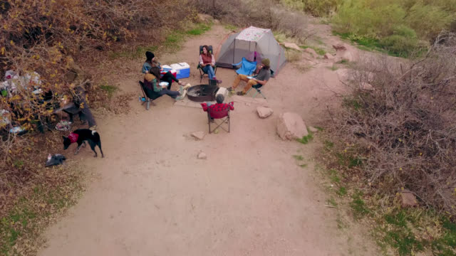 Drone shot over riverside camping site as group of friends sit and talk around fire pit.