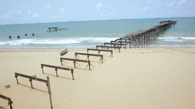 vídeos de stock e filmes b-roll de drone shot over the remains of an old jetty on a beach in lome, togo. - pontão