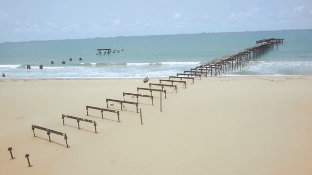 drone shot over the remains of an old jetty on a beach in lome, togo. - jetty stock videos & royalty-free footage