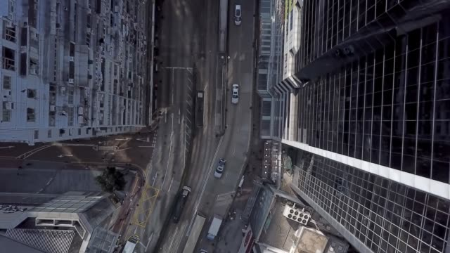 drone shot pan of busy hong kong streets and city buildings - fensterfront stock-videos und b-roll-filmmaterial