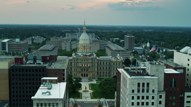 drone shot pulling back from michigan state capitol building over downtown lansing - lansing stock videos & royalty-free footage