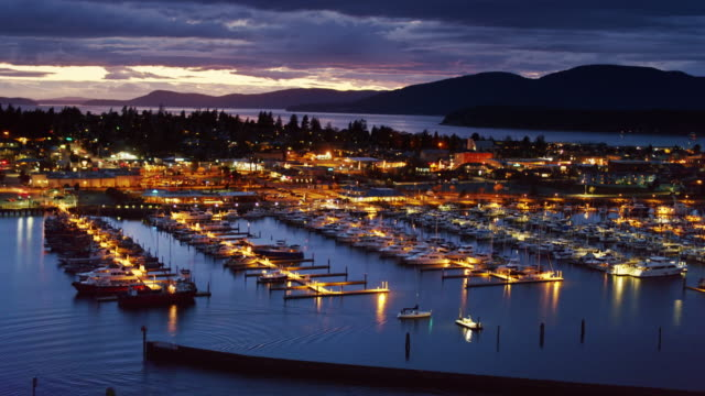 drone shot pulling back from small sailboat pulling in to anacortes marina at night - anacortes stock videos & royalty-free footage