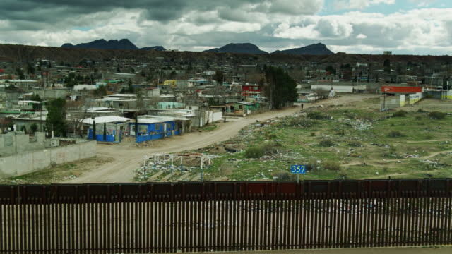 drone shot pulling back from us/mexico border wall and houses in anapra, mexico - mexico stock videos & royalty-free footage