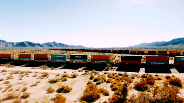 drone shot revealing a moving container train barreling down a railroad in the middle of the american desert. - tramway stock videos & royalty-free footage