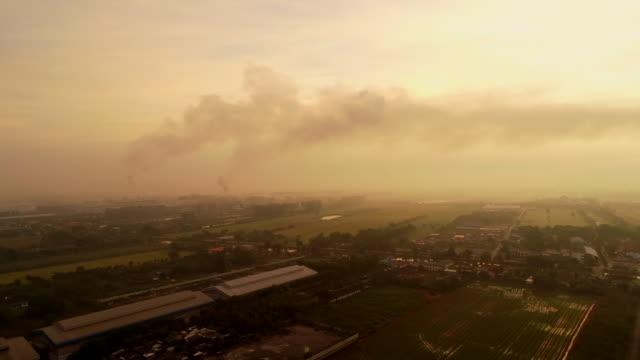 Drone abattu usine rurale le tube avec de la fumée au coucher du soleil hiver le matin.