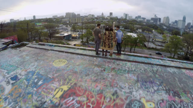 Drone shot soars over friends throwing hands in the air looking out over Austin, Texas skyline from Graffiti Park