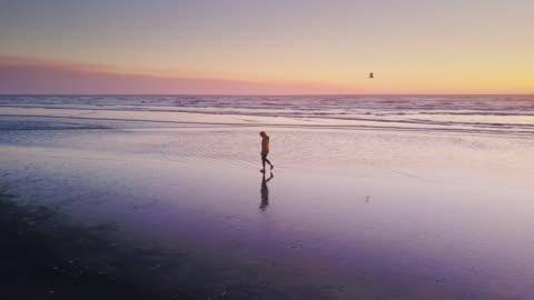 stockvideo's en b-roll-footage met drone shot - eenzame vrouw lopen op het strand bij zonsondergang - solitair