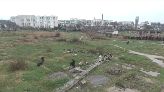 drone shot that captures volunteers scattered around the hills and shore of sevastopol crimea picking up trash - sevastopol crimea stock videos and b-roll footage