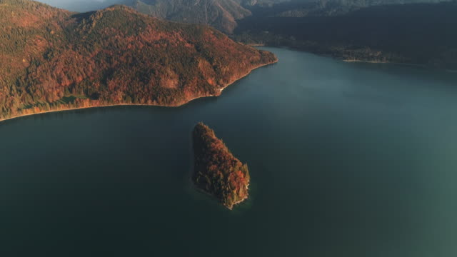 drone shot tilting down and moving towards an island in lake walchensee during autumn, germany - tourism stock-videos und b-roll-filmmaterial