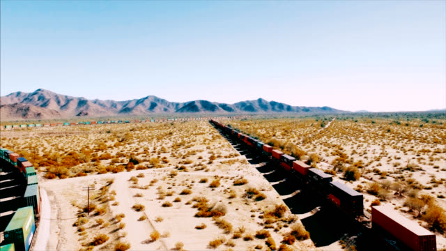 Drone shot tracking left to right over a container freight train as it barrels down a railroad in the arid American desert.