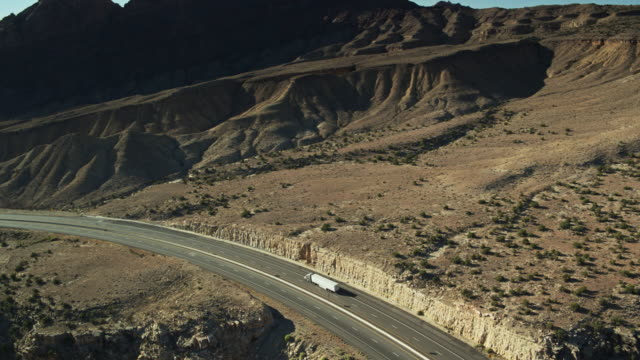 drone shot tracking truck along i-70 with reveal of the san rafael reef - san rafael swell stock videos and b-roll footage