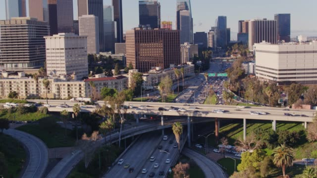 drone shot with upward tilt of four level interchange and downtown los angeles - motorway stock videos & royalty-free footage