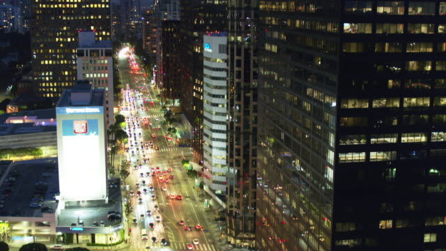 drone shot with upwards tilt along wilshire blvd, los angeles at night - westwood neighborhood los angeles stock videos & royalty-free footage