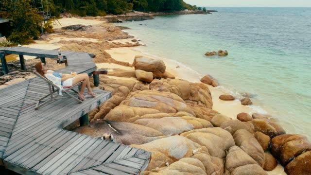 stockvideo's en b-roll-footage met drone schoot vrouw drankje een kokosnoot water op comfortabele stoel op het strand. - tropische drankjes