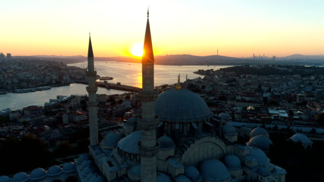vídeos de stock e filmes b-roll de drone shots of suleymaniye mosque and galata bridge on golden horn istanbul at sunrise - minarete