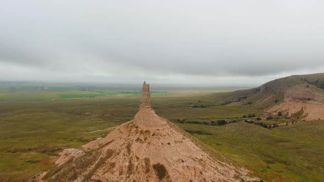 stockvideo's en b-roll-footage met drone slowly moves away from the top of the stone pillar at the green plains (chimney rock, nebraska, usa) - zandsteen