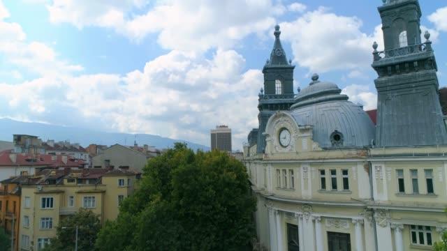 stockvideo's en b-roll-footage met drone stationaire onthullen klokkentoren kijken naar sky downtown district sofia, bulgarije - eastern european culture