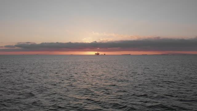 vídeos de stock, filmes e b-roll de drone sunset footage de uma plataforma de perfuração de petróleo e gás off-shore no oceano pacífico ao largo da costa sul da califórnia perto de huntington beach em los angeles - boca de poço