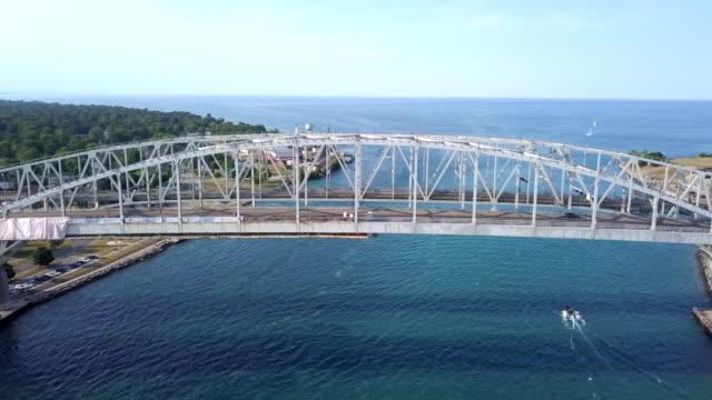 vídeos de stock e filmes b-roll de a drone sweeping view of the blue water bridge, st. claire river, sarnia, ontario and port huron - ontário canadá