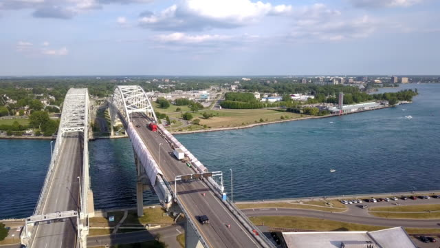 a drone sweeping view of the blue water bridge, st. claire river, sarnia, ontario and port huron - geographical border stock videos & royalty-free footage