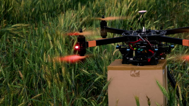 ds drone taking off with the package in the middle of a field - carrying stock videos & royalty-free footage