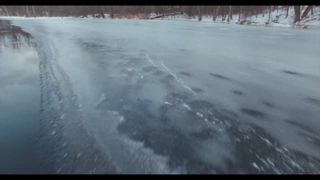 wxmi drone pov of the flat river partiallyfrozen lined by bare trees and snowcover ground near lowell michigan on feb 3 2017 - lowell stock videos & royalty-free footage