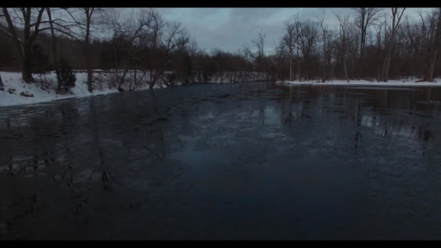 wxmi drone pov of the flat river partiallyfrozen lined by bare trees and snowcover ground near lowell michigan on feb 3 2017 - michigan stock videos and b-roll footage