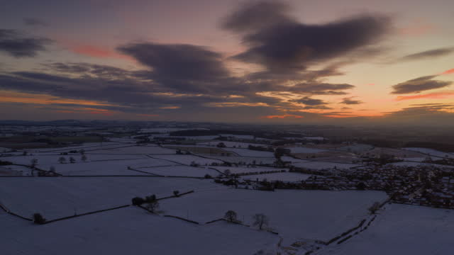 drone time lapse flying over a rural scene covered in snow at sunset, england, united kingdom - staffordshire england stock videos & royalty-free footage