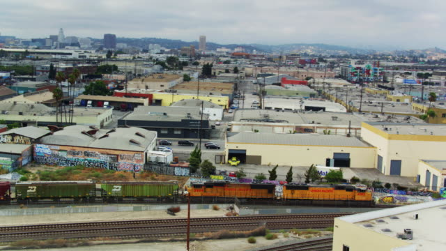 vídeos de stock e filmes b-roll de drone tracking shot of freight train on the alameda corridor with downtown la skyline - expansão urbana
