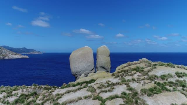 vídeos y material grabado en eventos de stock de 4k drone tracking shot of massive boulders within seascape - brightly lit