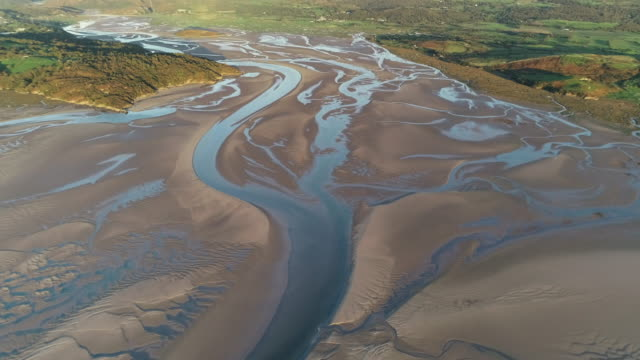 drone tracking shot showing an estuary in borth-y-gest at low tide, wales, united kingdom - low tide stock videos & royalty-free footage