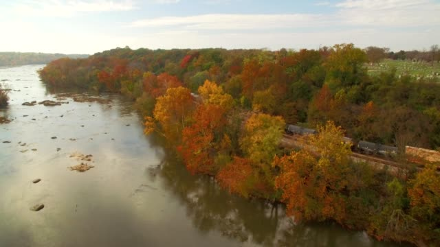 drone - train parked along an autumn riverbank - richmond virginia stock videos & royalty-free footage