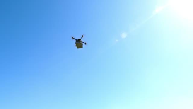 晴れた空を横切ってパッケージを運ぶドローン - 小荷物点の映像素材/bロール