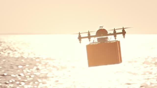 日差しの中で海面の上のパッケージを輸送 SLO MO ドローン