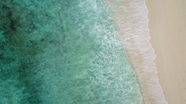 drone travel video: drone view still lagoon waves beach