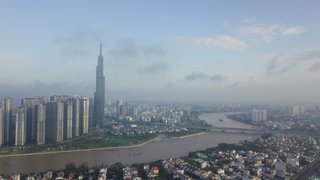 4k drone video flying over ho chi minh city skyline and skyscraper in center of heart business at ho chi minh city downtown. panorama of cityscape on saigon river in ho chi minh city at vietnam in morning - ho chi minh city stock videos & royalty-free footage