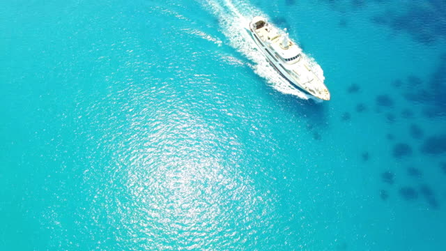drone video of a white ship travelling across the turquoise ocean - helicopter tour stock videos and b-roll footage
