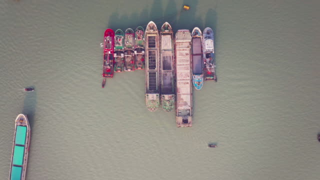 vídeos de stock e filmes b-roll de drone video of cargo ships parking in the middle of the river - embarcação comercial